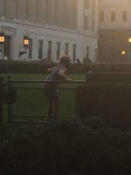 A woman appearing to be Dean Cristen Scully-Kromm crouching after finishing a vault over a closed fence onto a Butler south lawn.